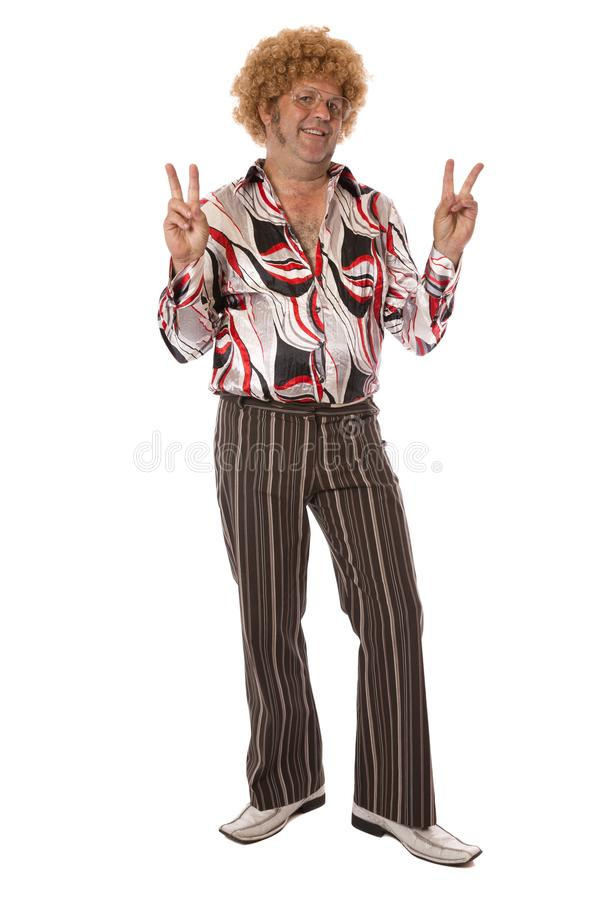 Groovy Peace Man. A man dressed in the outrageous style of seventies clothing giving a hippy peace sign royalty free stock image