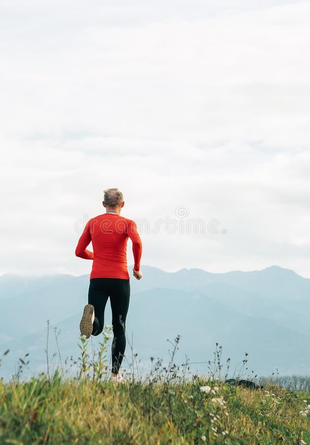 Man dressed in red long sleeve shirt runs by the road with mountain background vertical shoot stock images