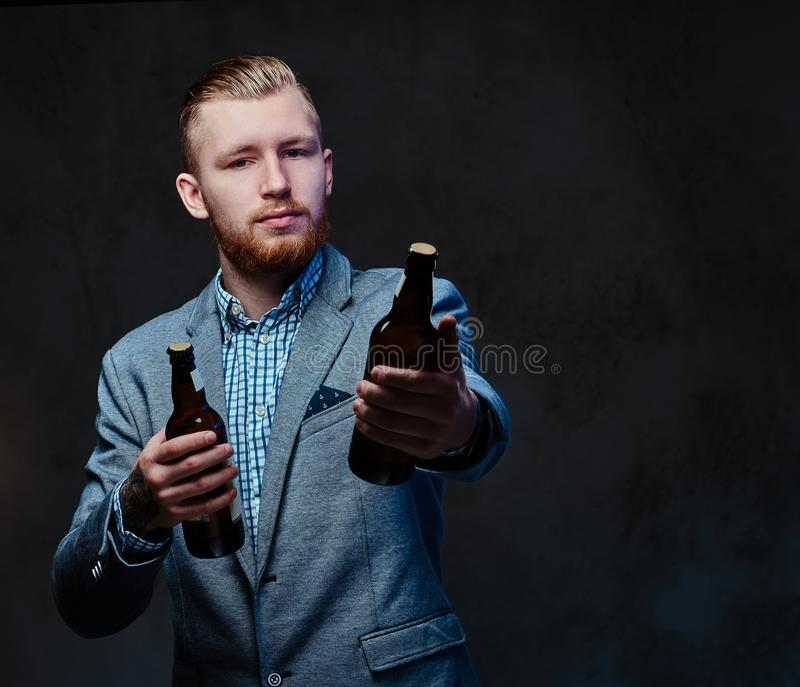A man dressed in a suit holds a bottle with craft beer. Stylish redhead bearded male dressed in a suit holds a bottle with craft beer over grey background royalty free stock photos
