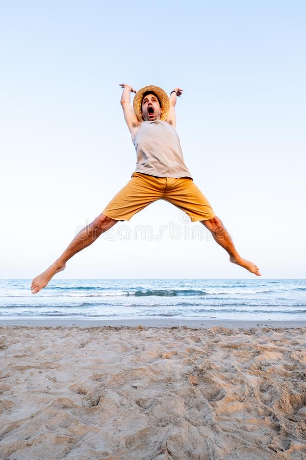 Man dressed in summer clothes jumps on the sand of a Mediterranean beach at sunset stock photography