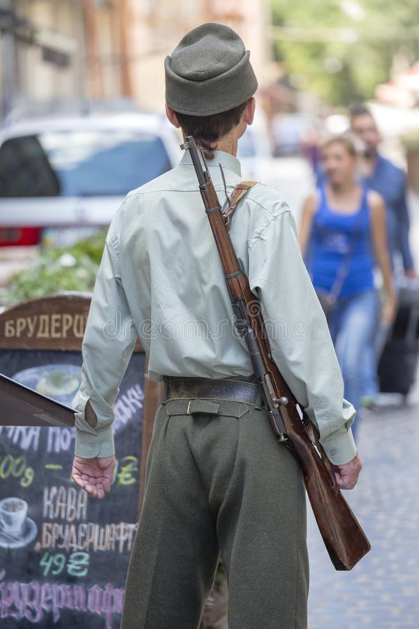 Man dressed in the uniform of the Ukrainian insurgent army with a rifle invites tourists to enter the restaurant on the street in royalty free stock photography