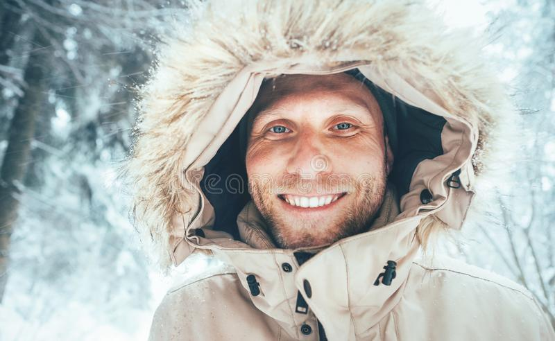 Man dressed in Warm Hooded Casual Parka Jacket Outerwear walking in snowy forest cheerful smiling face portrait. Outdoor time and. Winter outfit concept image royalty free stock photos