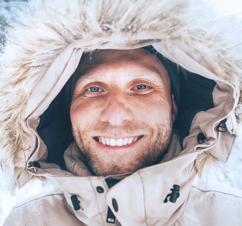 Man dressed in Warm Hooded Casual Parka Jacket Outerwear walking in snowy forest cheerful smiling face portrait. Outdoor time and. Winter outfit concept image stock image