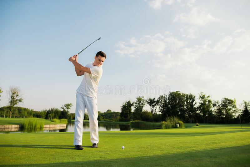 An athlete in a white suit took a golf club to strike stock images