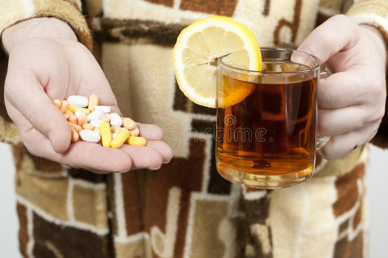 A Man In A Dressing Gown Holds A Handful Of Pills And A Hot Tea With ...