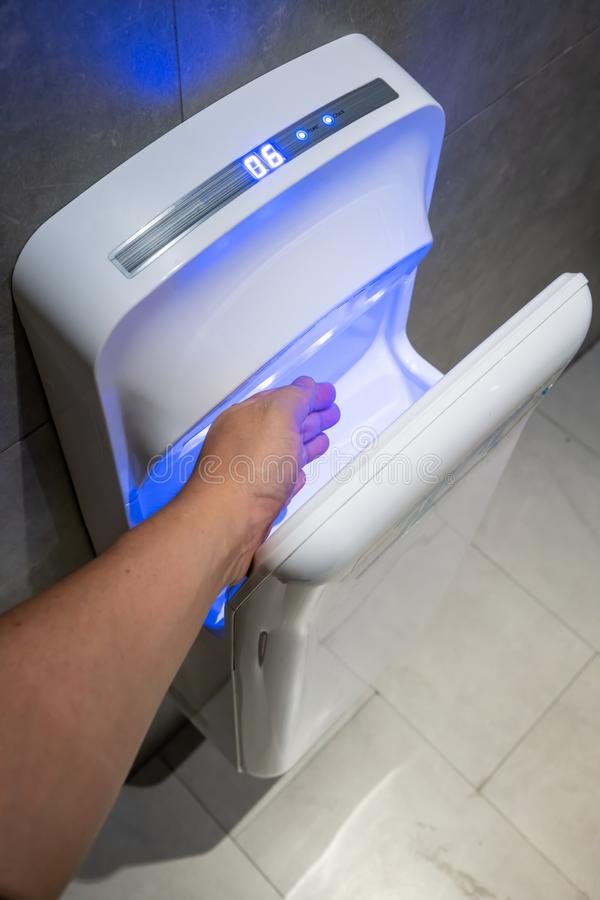 Man dries wet hand in modern vertical hand dryer in public restroom royalty free stock photography