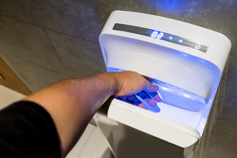 Man dries wet hand in modern vertical hand dryer royalty free stock photos