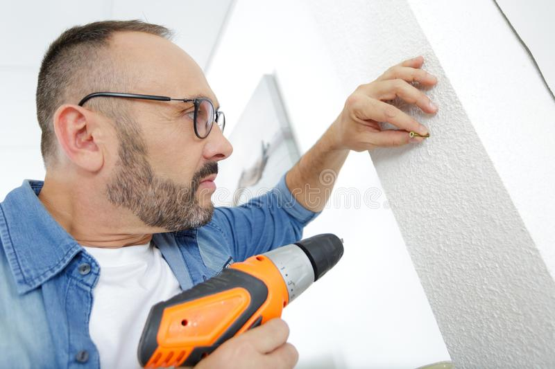 Man drilling wall with drill perforator. Man drilling the wall with drill perforator royalty free stock photo