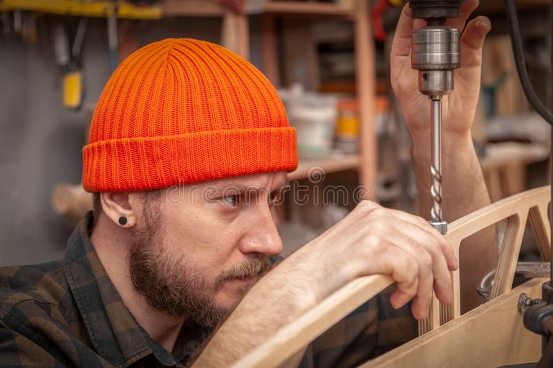 Handicraft Carpentry. Man drilling wood with  Drill machine on the table in renovation work at home. Home repair concepts, close up royalty free stock photography