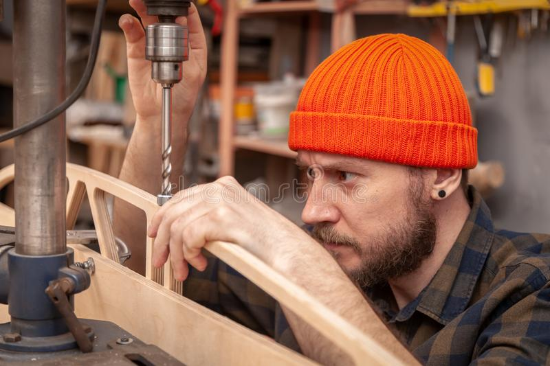 Handicraft Carpentry. Man drilling wood with  Drill machine on the table in renovation work at home. Home repair concepts, close up royalty free stock image