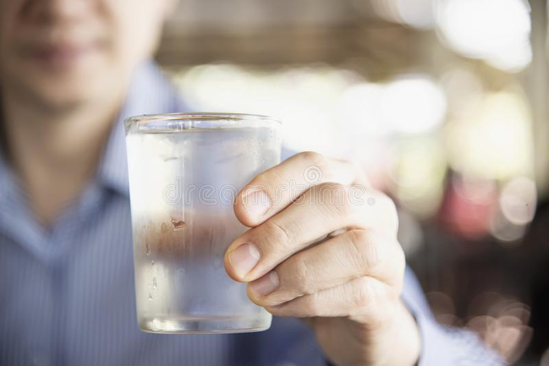 Man drink fresh cold pure water in glass. With a blur background stock photo