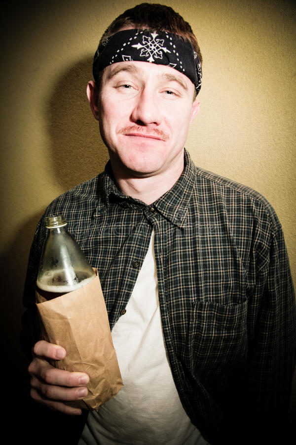 Man Drinking Alcohol. A man drinking alcohol from a bottle in a paper bag royalty free stock photos