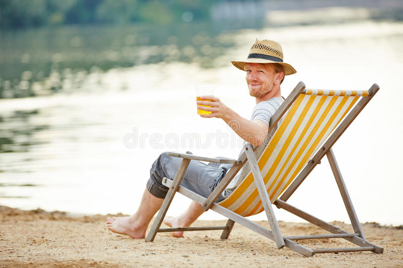 Man drinking beer in deck chair stock photography