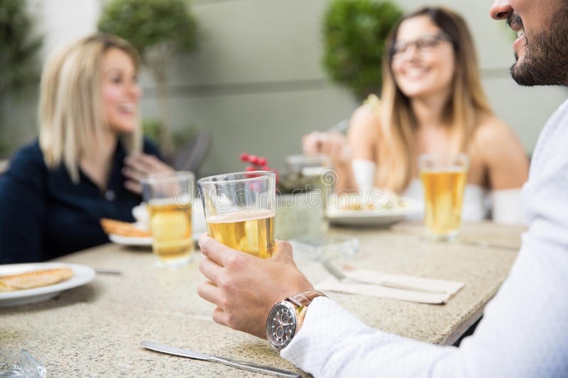 Man drinking beer with some friends royalty free stock image