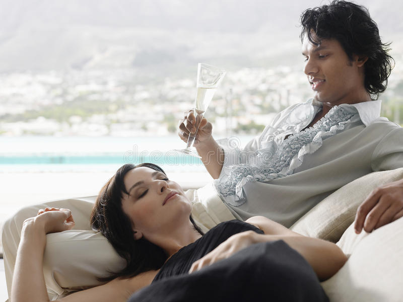 Download Man Drinking Champagne With Woman Lying On His Lap Stock Image - Image: 33906991