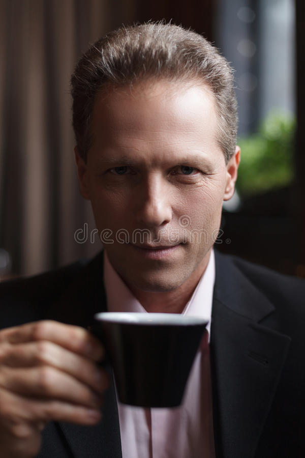 Man drinking coffee. Confident mature businessman drinking coffee at the restaurant royalty free stock photography