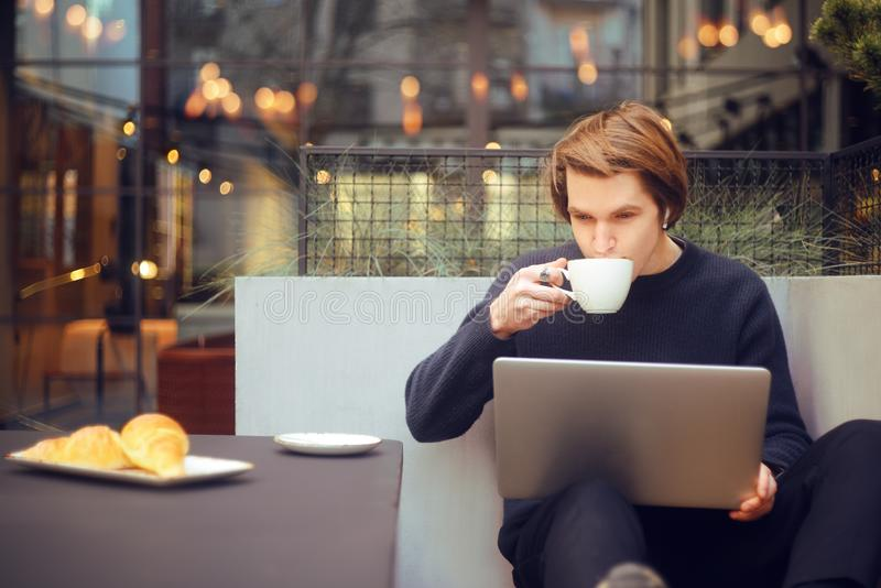 Man drinking coffee in a restaurant on the terrace. Freelancer outdoor with a laptop, has breakfast with croissants. Young stock photos