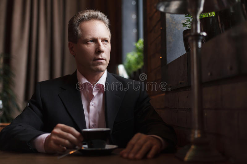 Man drinking coffee at the restaurant Thoughtful mature business stock photo