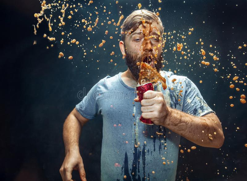Man drinking a cola and enjoying the spray. royalty free stock images