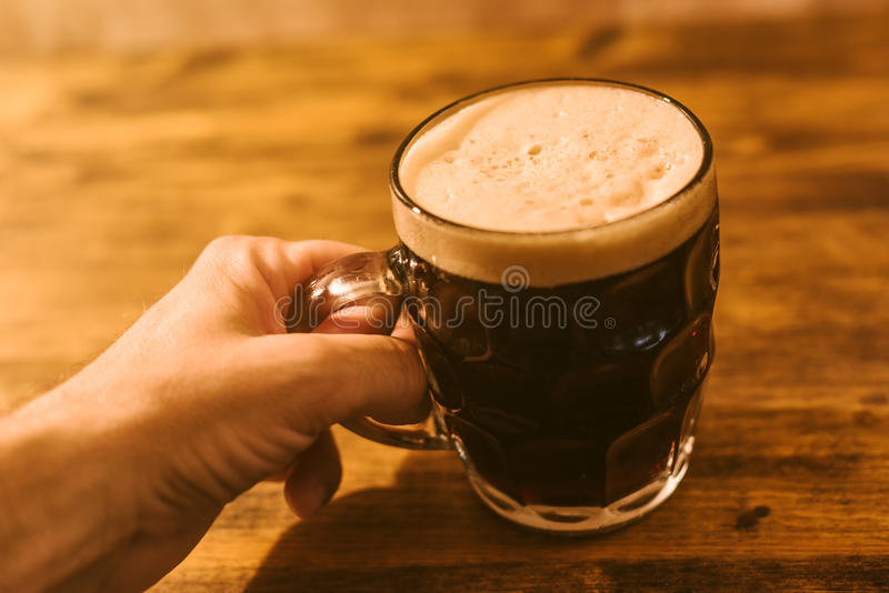 Man drinking dark beer in british dimpled glass pint mug stock images