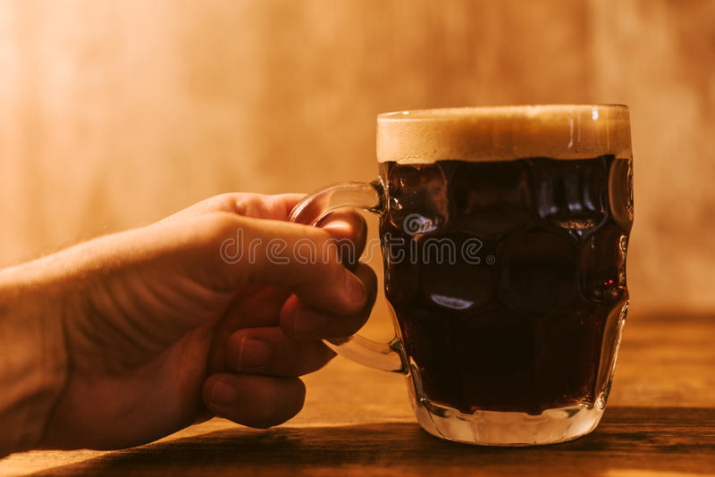Man drinking dark beer in british dimpled glass pint mug stock photo