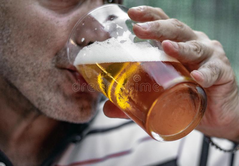 Man drinking a glass of good cold beer. adult with a beard stock photo