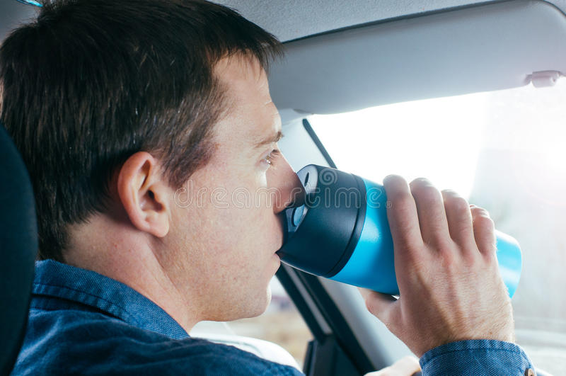 Man drinking hot coffee from thermo mug in a car stock image