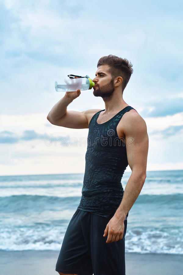 Man Drinking Refreshing Water After Workout At Beach. Drink. Man Drinking Water After Running Workout At Beach. Portrait Of Thirsty Healthy Athletic Male With royalty free stock images