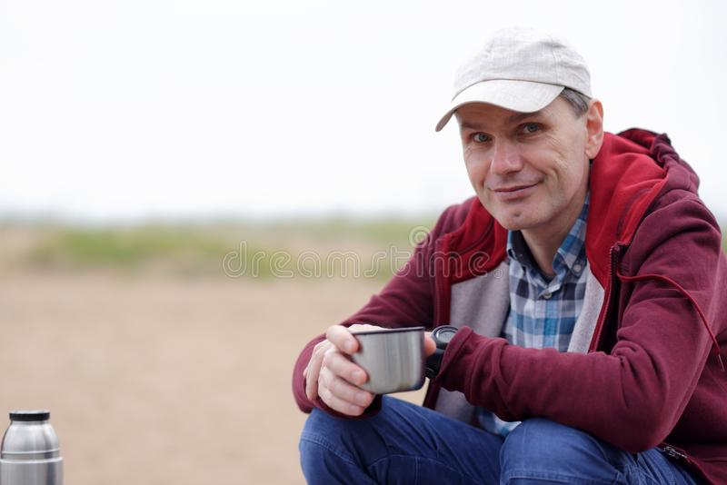 Man drinking tea on a beach royalty free stock photo