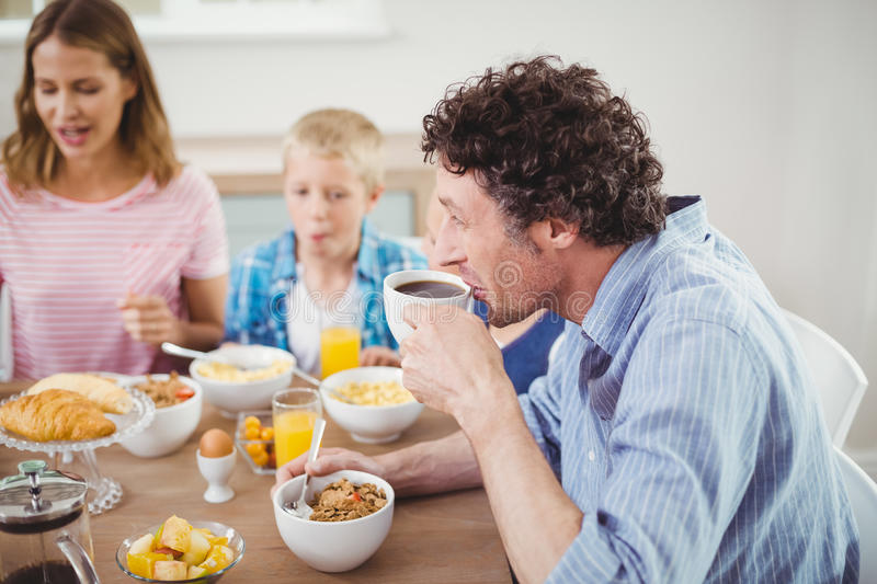Man drinking tea during breakfast with family royalty free stock photos