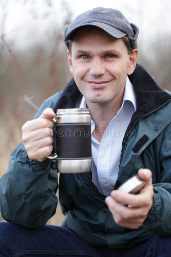 Man drinking tea outdoors stock photo