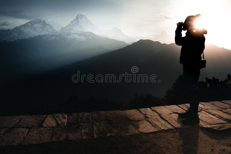 A man drinking a tea during sunrise and surrounded by mountains royalty free stock images