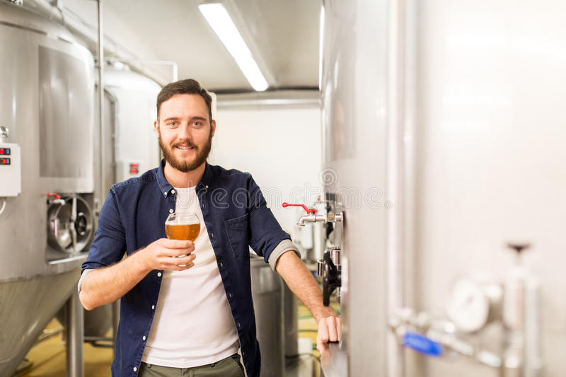 Man drinking and testing craft beer at brewery. Alcohol production, manufacture, business and people concept - man drinking and testing craft beer at brewery royalty free stock photos
