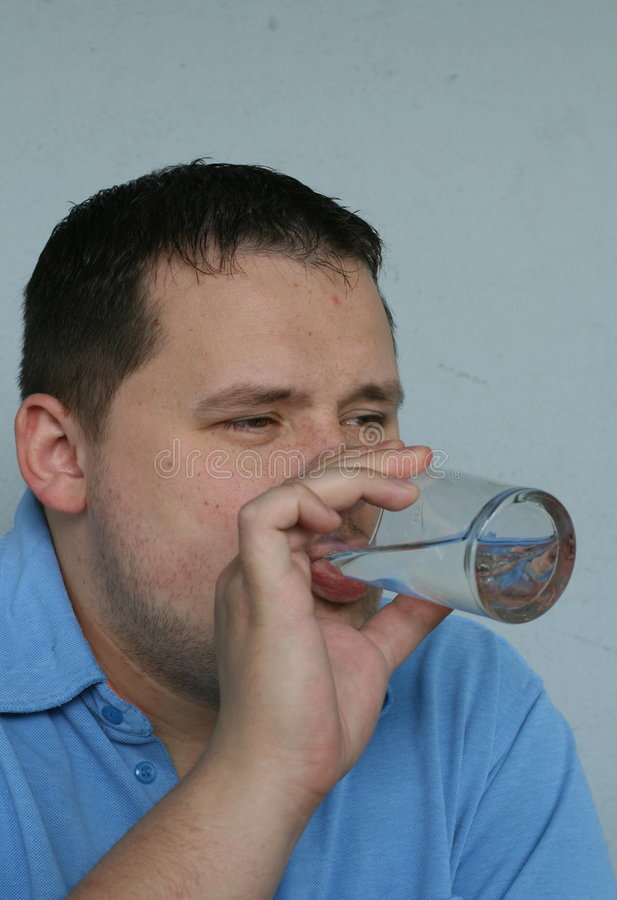 Man Drinking Water. Over weighted man drinking glass of water stock photo
