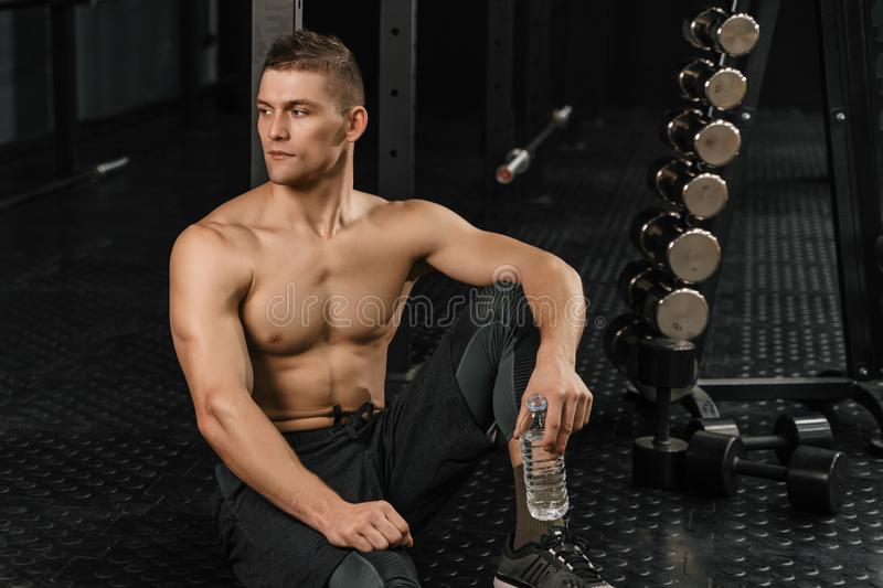 Man drinking water in a gym after crossfit training. Man drinking water in a gym after hard crossfit training stock images