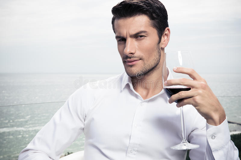 Man drinking wine outdoors. Handsome young man drinking wine outdoors stock photos