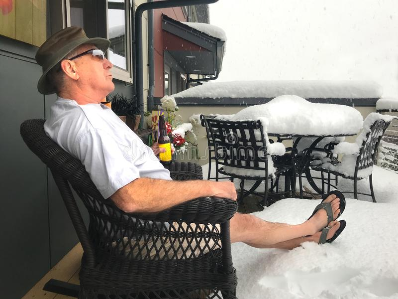 Man Drinks Beer in Snow Storm During a Northwest Summer. Senior man enjoys beer on shorts, hat and flip-flops in the midst of snow storm in the Pacific Northwest royalty free stock photos