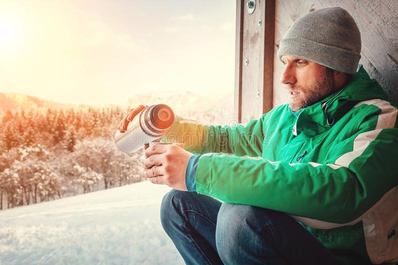 Man drinks a hot drink worker ot traveler on open winter air stock photography