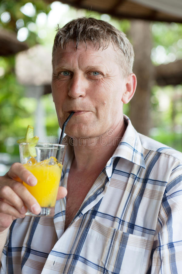 Man drinks orange juice stock images