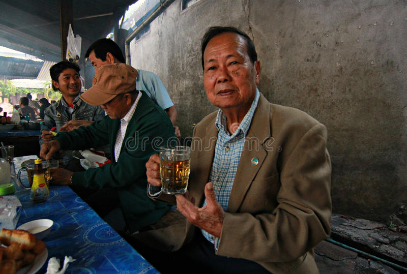 Man Drinks tea from Beer Mug in Luang Prubang, Laos royalty free stock photography