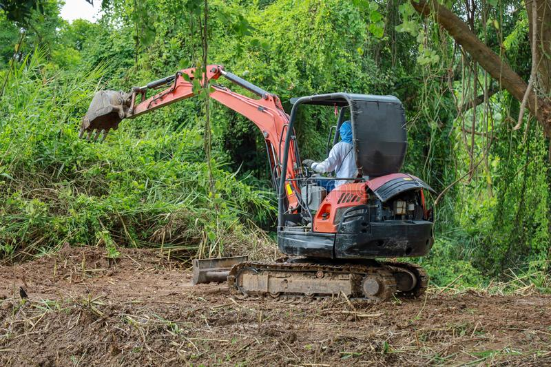 The man drive Backhoe clear nature for make the soil road in thailand royalty free stock photo