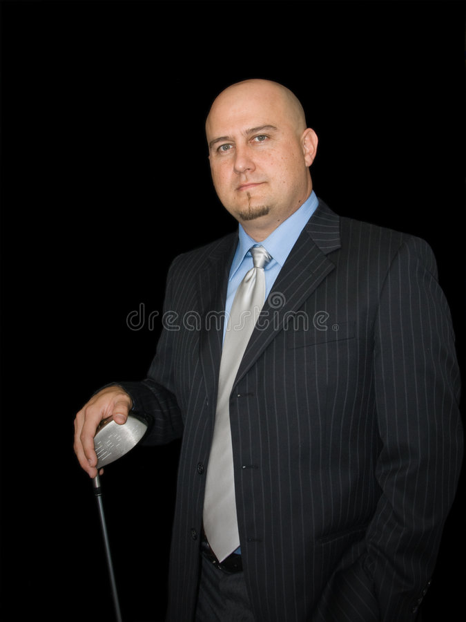 Man With Driver. Man in business suit against dark background leans on golf club stock photography