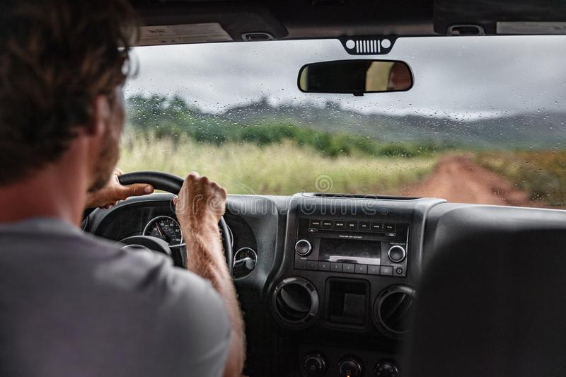 Man driver driving off road trail path with 4x4 car on adventure trip travel holiday. Hawaii drive in the rain. Bad weather stock photo