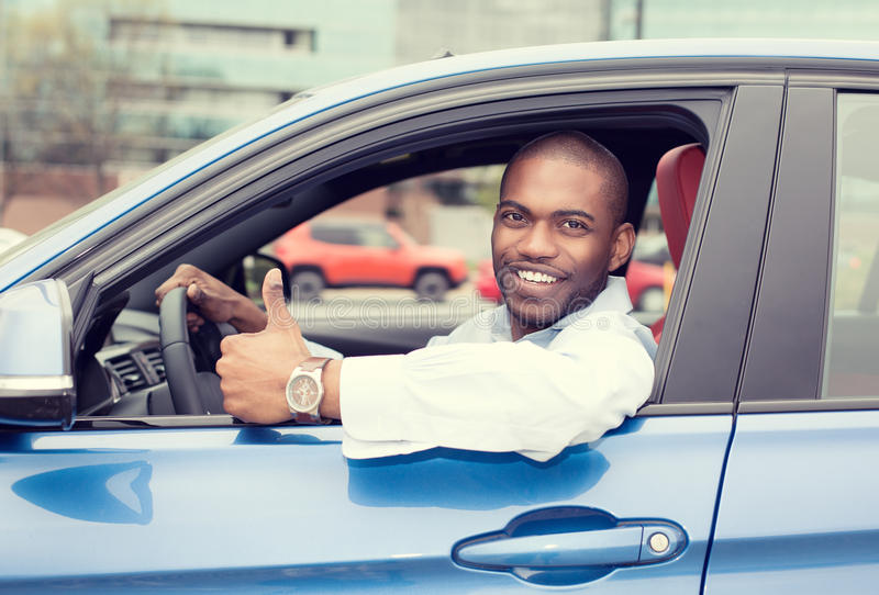 Man driver happy smiling showing thumbs up driving sport blue car. Car side window. Man driver happy smiling showing thumbs up driving sport blue car isolated royalty free stock photography