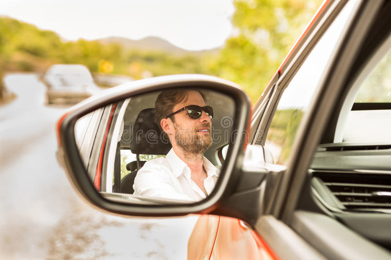 Man (driver) reflected in a car wing mirror. Happy smiling forty years old caucasian man (driver) reflected in a car wing mirror. Summer day and road in royalty free stock photos