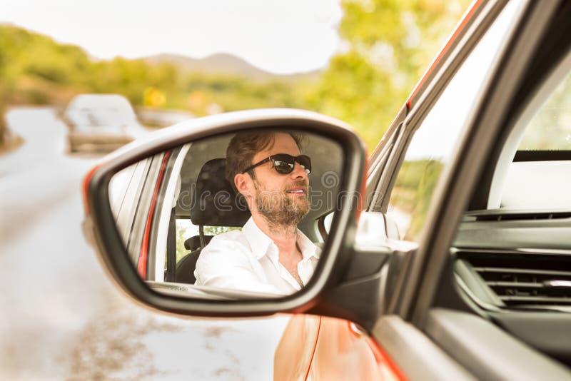 Man & x28; driver& x29; reflekterat i en bilvingspegel royaltyfria foton