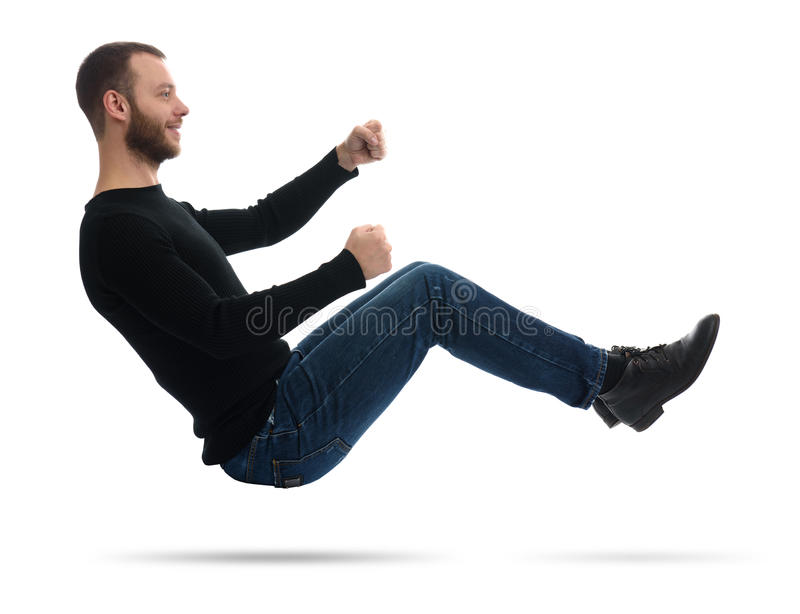 Man drives an imaginary car. Guy drives an imaginary car. man in the air. Isolated on white stock photography
