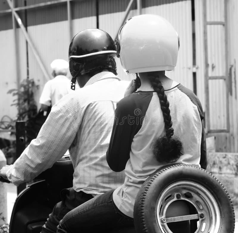 Man is driving a bike black & white stock photograph. A man is driving a bike with a lady behind on the streets of Kolkata, India stock photograph stock photo