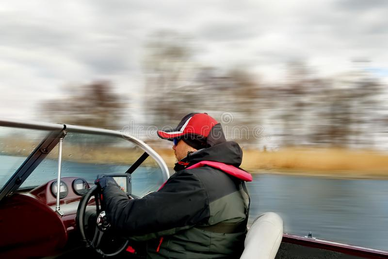 A man driving a boat at high speed rushes along the river. Smeared from speed terrain. Soft focus. royalty free stock photo