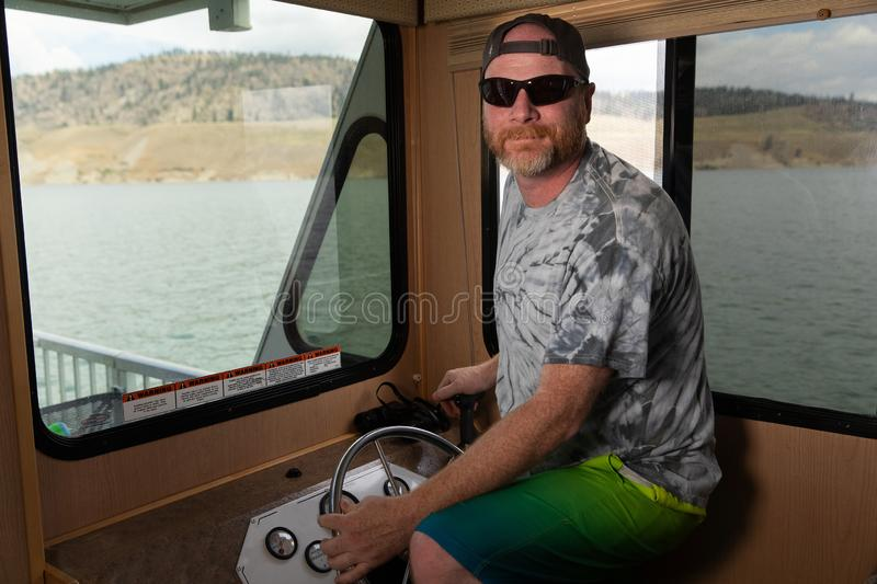 Man driving a boat on a lake. Man behind the wheel in the cabin of a boat on a lake royalty free stock images